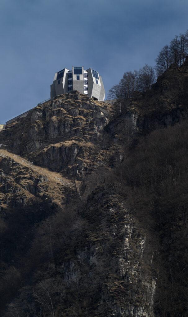 """Als eine """"Blüte aus Stein"""" beschreibt Mario Botta seinen Entwurf für den Neubau auf dem Plateau des Monte Generoso. Gleichsam einer Blüte öffnet sich das Gebäude denn auch zum Licht. Die großflächigen Vertikalverglasungen müssen in dieser exponierten Lage extremen Wind- und Schneelasten standhalten. Mit hochbelastbaren Stahlprofilen konnte die Tragstruktur sehr schlank und hoch wärmedämmend ausgeführt werden."""