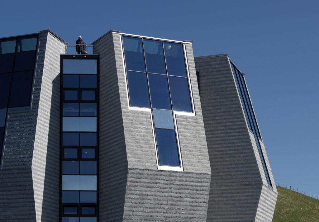 Panoramaverglasungen aus Jansen VISS HI TVS, 60 mm. Vertikale Fensterbänder aus VISS HI TVS 50 mm, mit Öffnungsflügeln Schüco AWS 75 SI+ und Edelstahl-Füllelementen im Anschlussbereich der Decken.