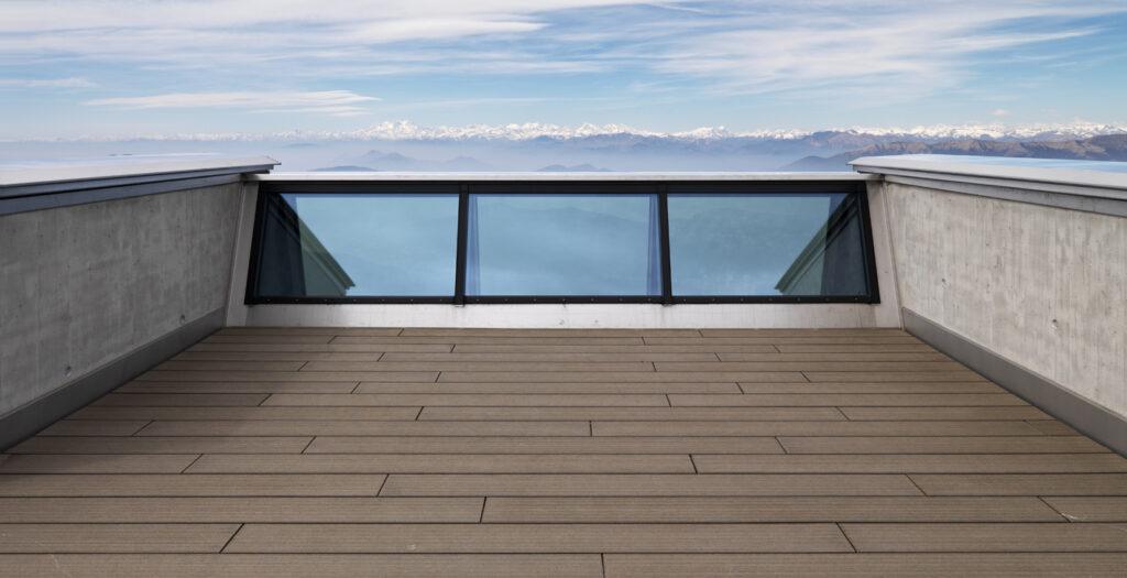 Der obere Bereich der Panoramaverglasung zieht sich bis auf Brüstungshöhe der Dachterrasse. Als innere Brüstung wurde eine zweite Verglasung aus dem gleichen Profilsystem V-förmig dagegengesetzt.