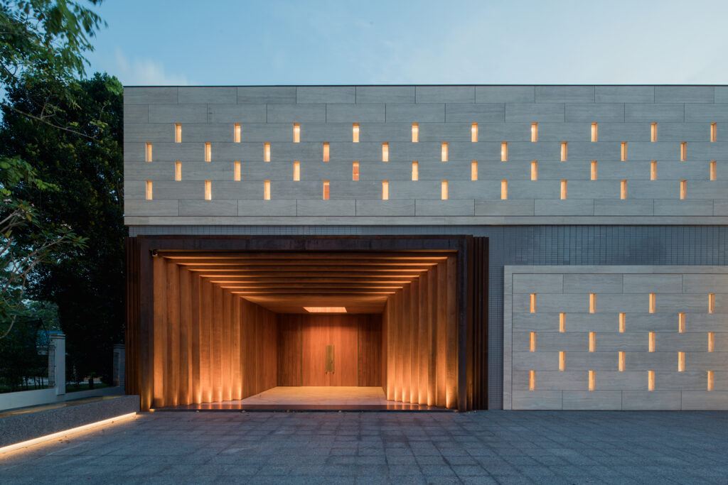 Die mit Travertinplatten verkleidete, dezent perforierte Haupteingangsfassade befindet sich auf der Straßenseite. Unterhalb der Eingangsebene sind sekundäre Nutzungsbereiche, u. a. eine Tiefgarage, untergebracht.
