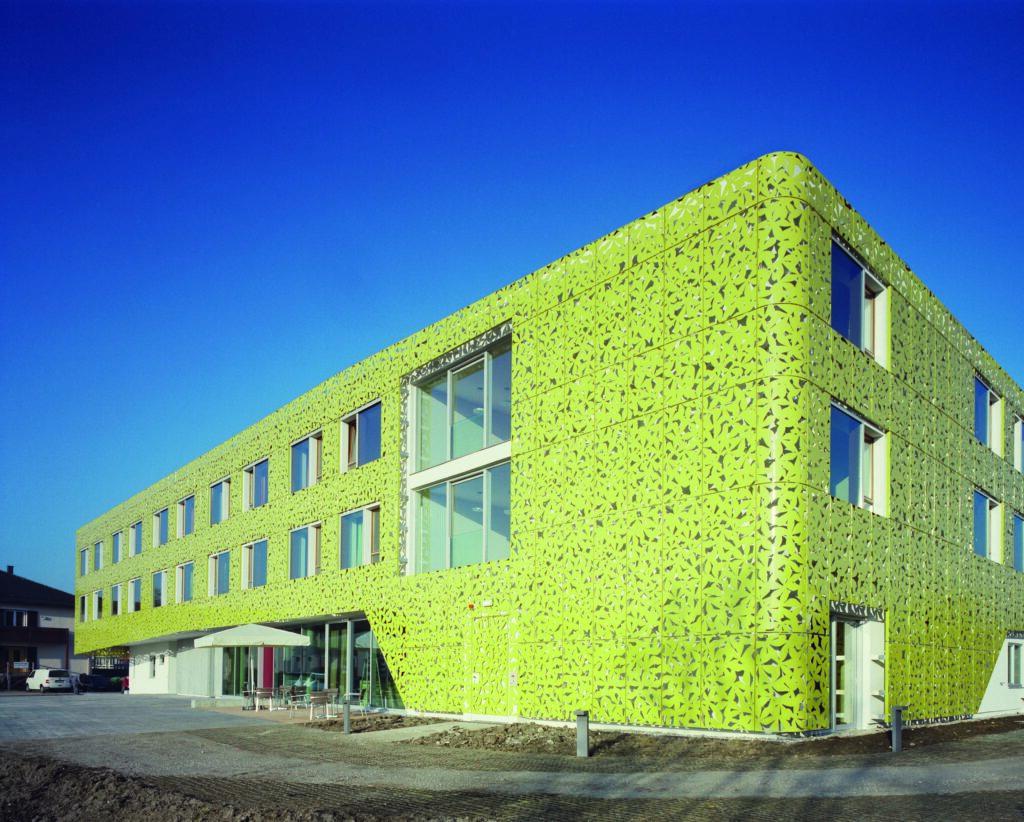 Neubau Gesundheitszentrum Seekirchen im Salzburger Land. Blick von außen – ein grünes Kleid für ein großes Haus in kleinteiligem Umfeld.